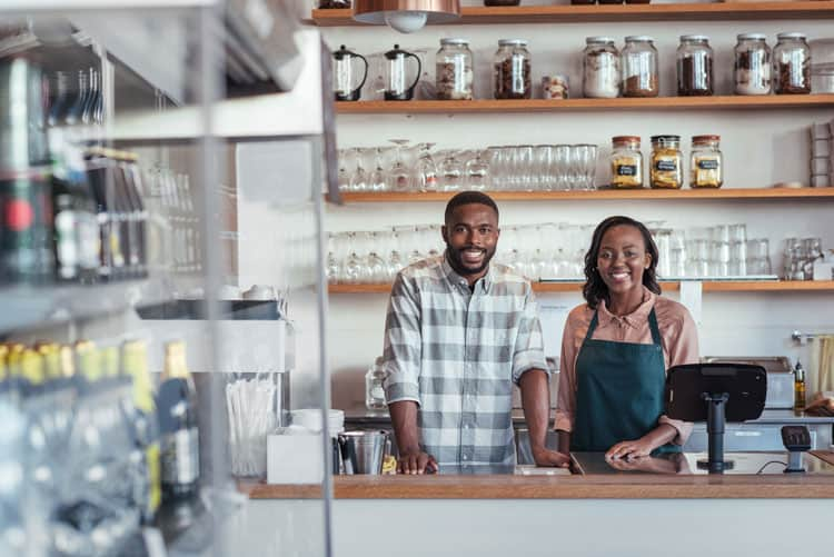 young black couple behind store counter